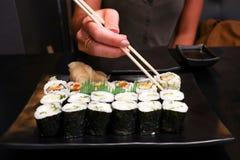 一个女孩在日本咖啡馆坐并且吃着与筷子的鲜美寿司在有茶碟的一个黑色的盘子在黑桌上 免版税库存照片