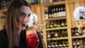 一个女孩在时尚餐馆,喝红色异乎寻常的鸡尾酒的妇女喝在一张桌上的一个鸡尾酒 股票录像