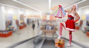一个女孩在有礼物包裹的圣诞老人服装在bac的 库存照片
