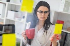 一个女孩在有贴纸的一个委员会附近在她的手上站立并且拿着一个红色杯子 库存照片