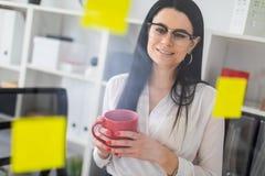 一个女孩在有贴纸的一个委员会附近在她的手上站立并且拿着一个红色杯子 免版税库存照片