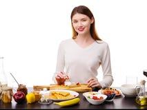 一个女孩在比利时华夫饼干放置草莓 免版税库存图片
