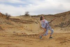 一个女孩在沙漠播放一个虚构的吉他重的岩石 免版税图库摄影