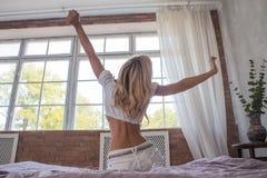 一个女孩在现代卧室时舒展,当叫醒坐与后面的床清早看窗口 库存照片