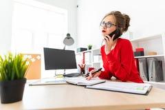 一个女孩在电话在她的手上站立在一张桌上在办公室,拿着一个黑标志并且谈话 2th混淆女孩岁月 免版税图库摄影
