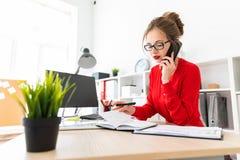 一个女孩在电话在她的手上站立在一张桌上在办公室,拿着一个黑标志并且谈话 2th混淆女孩岁月 库存照片