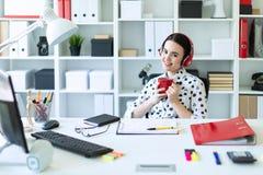 一个女孩在耳机在她的手和微笑上坐在一张桌上在办公室,拿着一个红色杯子 免版税库存照片