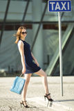 一个女孩在购物以后乘坐一辆出租汽车 愉快 免版税库存照片
