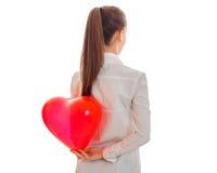 一个女孩在他的在大红色心形的气球后的手上举行 库存图片