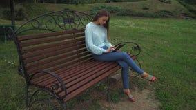 一个女孩坐一张公园长椅和重击页在您的片剂 股票录像