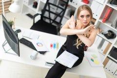 一个女孩坐一张桌在办公室,拿着一支笔和一种片剂有板料的并且抓手在前面 库存照片