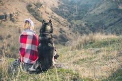 一个女孩坐与她的朋友多壳的狗在峡谷边缘在日落 免版税库存照片