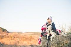 一个女孩坐与她的朋友多壳的狗在峡谷边缘在日落 库存图片