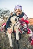 一个女孩坐与她的朋友多壳的狗在峡谷边缘在日落 免版税库存图片