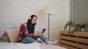 一个女孩坐与耳机的床,谈话在智能手机,笑,讲一个有趣的故事 股票视频