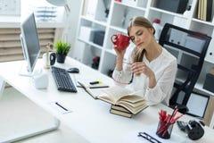 一个女孩坐在一张桌上在办公室并且拿着一个杯子在一只手上和在其他玻璃 图库摄影