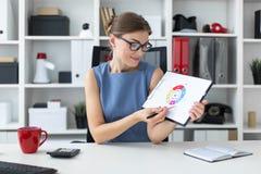 一个女孩坐在一张桌上在办公室并且拿着一支笔和一个文件与图 图库摄影