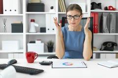 一个女孩坐在一张桌上在办公室并且看与图的一个文件 库存图片