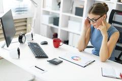 一个女孩坐在一张桌上在办公室并且看与图的一个文件 库存照片
