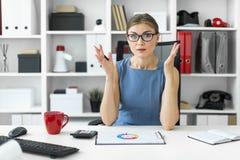 一个女孩坐在一张桌上在办公室并且看与图的一个文件 免版税库存图片
