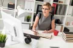 一个女孩坐在一张桌上在办公室,拿着一支铅笔和一个红色杯子在她的手上 在女孩前说谎  免版税库存图片