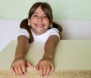 一个女孩坐在书桌 库存照片