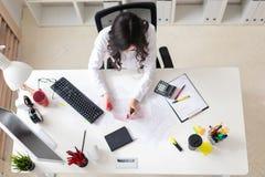一个女孩坐在办公室桌上并且做一个桃红色标志在本文的重要图 库存图片
