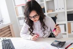 一个女孩坐在办公室桌上并且做一个桃红色标志在本文的重要图 免版税图库摄影