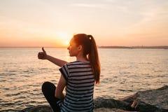 一个女孩坐岩石在海旁边在日落并且显示手标志哪些意味凉快 休息,假期 图库摄影