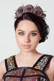 一个女孩布鲁内特的画象有头发射线的与精美由与刺岩石的黑玫瑰组成和在她的头发的一个花圈 库存图片