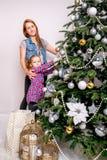 一个女孩帮助她的母亲装饰家庭圣诞树 免版税库存照片
