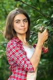 一个女孩户外坐在树,沉思的神色,一个夏日的草户外在公园 免版税库存照片