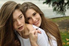 一个女孩拥抱其他从后面,微笑 库存图片