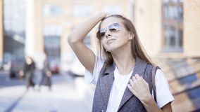 一个女孩拿着在修理她的头发之外的太阳镜 免版税库存图片