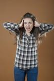 一个女孩握在他的头后的手并且尖叫 免版税库存照片