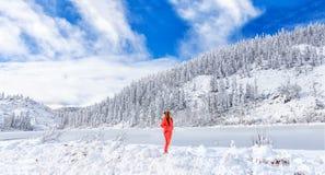 一个女孩敬佩在湖的冬天风景 taiga小山的美丽的湖Amut在及早俄罗斯的远东 免版税库存照片