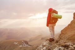 一个女孩旅客立场岩石高在高加索的山反对岩石落日背景和 免版税库存照片