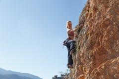 一个女孩登山人在Geyikbayiri Tur攀登峭壁的上流 免版税库存图片