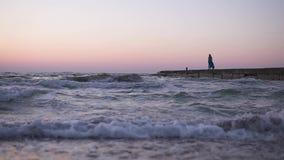 一个女孩的偏僻的剪影振翼的衣裳的沿海码头走在黎明,反对上升 股票视频