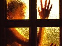 一个女孩的剪影在玻璃门后的 免版税库存照片