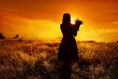一个女孩的剪影形象有花束的在与蓬松草的领域在日落 在黄昏的黑暗的照片 免版税库存图片