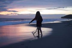 一个女孩的剪影日落的 免版税图库摄影