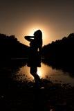 一个女孩的剪影晚上太阳的 免版税库存照片