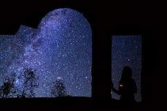 一个女孩的剪影有一个蜡烛的аnd与银河的满天星斗的天空 免版税库存图片