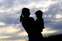 一个女孩的剪影有一个婴孩的在晚上 免版税库存照片