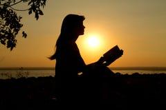 一个女孩的剪影有一本书的在日落 库存图片