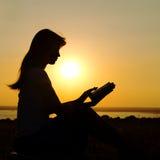 一个女孩的剪影有一本书的在日落 免版税库存图片