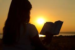 一个女孩的剪影有一本书的在日落 免版税库存照片