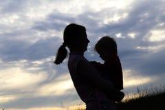 一个女孩的剪影有婴孩的 免版税库存图片