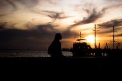 一个女孩的剪影江边的 一艘老船的剪影在背景中 女孩等待船 免版税库存图片